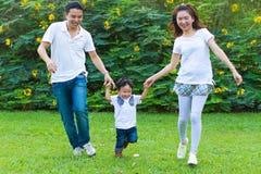 在公园结合与他们的年轻儿子的赛跑 免版税库存图片