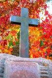 在公墓在秋天光的墙壁附近站立一个黑石十字架 图库摄影