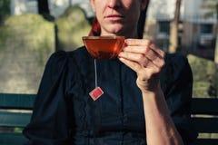 在公墓的妇女饮用的茶 免版税库存图片