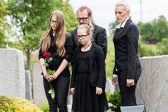 在公墓的家庭哀悼被死亡的亲戚的 免版税图库摄影