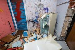 在公寓废墟的一把大锤杀害的老冰箱  免版税图库摄影