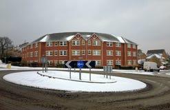在公寓楼前面的雪盖的交通环形交通枢纽 库存照片