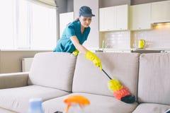 在公寓的仔细和被集中的更加干净的工作 她使用在沙发的尘土刷子 女孩清洗柔和 她到达 库存照片