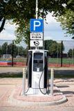 在公开停车处的电动车汽车充电站 免版税库存照片