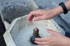 在公开喷泉的妇女洗涤的手 库存照片