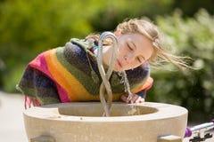 在公开喷泉的白肤金发的女孩饮料 库存照片