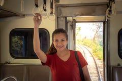 在公开火车里面的亚洲妇女藏品扶手栏杆有空位进去的在度假 图库摄影