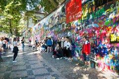 在公开街道画列侬墙壁前面的人们在查理大桥, Mala Strana附近在布拉格,捷克 免版税库存图片