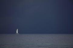在公海的帆船在晚上 库存图片