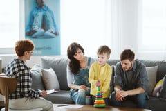 在关于他们的孩子的一次会议期间父母和治疗师坐长沙发 免版税库存照片