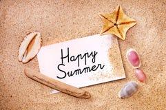 在关于白色海滩沙子的笔记写的愉快的夏天 免版税库存图片