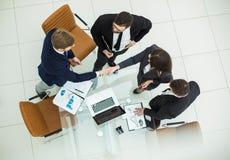 在关于财政合同的讨论的以后可靠握手商务伙伴在办公室 库存照片