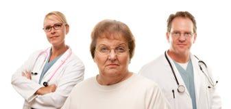 在关心的医生前辈妇女之后 库存照片