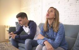 在关系问题的年轻有吸引力的夫妇的互联网手机赌博的上瘾者男朋友忽略哀伤忽略的和bo 库存照片