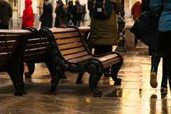 在其中一条街道在莫斯科,湿为雨,计算的伪造的长凳 在路人漫步附近 免版税库存图片