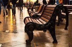 在其中一条街道在莫斯科,湿为雨,计算的伪造的长凳 在路人漫步附近 库存图片