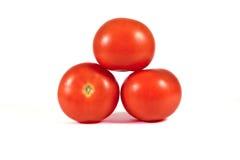 在其中每一的三个红色蕃茄在金字塔形状宏指令或关闭 免版税库存图片