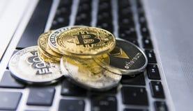 在其他隐藏硬币上面的Bitcoin硬币在膝上型计算机键盘的  Bitcoin金黄硬币 Cryptocurrency投资 免版税库存照片