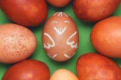 在其他鸡蛋中间的滑稽的鸡复活节彩蛋反对绿色背景 免版税库存照片