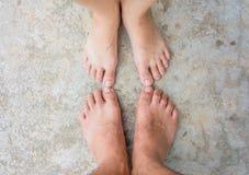 在具体地面关闭的夫妇脚 图库摄影