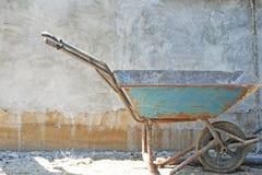 在具体块墙壁背景的老蓝色独轮车 免版税库存图片