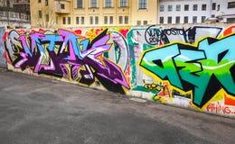 在具体篱芭绘的五颜六色的混乱街道画文本 免版税库存图片