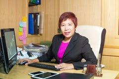 在典雅书桌的看起来的女商人亚裔经理资深年龄选址 免版税库存照片