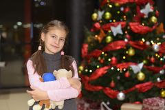 在典雅的圣诞树附近的十几岁的女孩身分与礼物 库存照片