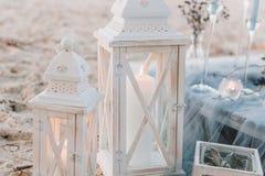 在典雅的桌设定旁边的大蜡烛在海滩婚礼的蓝色柔和的淡色彩 免版税图库摄影