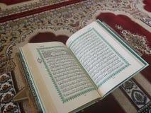 在典雅的波斯地毯的古兰经-与英文译文的阿拉伯文本 免版税图库摄影