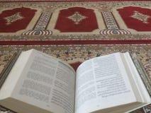 在典雅的波斯地毯的古兰经-与英文译文的阿拉伯文本 库存照片