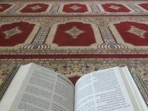 在典雅的波斯地毯的古兰经-与英文译文的阿拉伯文本 免版税库存图片