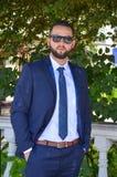 在典雅的蓝色衣服的严肃的年轻商人 免版税库存图片