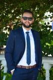 在典雅的蓝色衣服的微笑的年轻商人 免版税库存图片