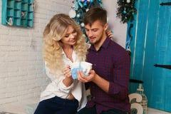 在典雅的衣裳的嫩夫妇,坐在圣诞树旁边在舒适家 库存照片