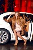 在典雅的配件礼服时兴的时髦的开会的美好的年轻性感的白肤金发的佩带的晚上构成在昂贵的汽车客舱  库存图片