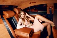 在典雅的配件礼服时兴的时髦的开会的美好的年轻性感的白肤金发的佩带的晚上构成在昂贵的汽车客舱  免版税库存照片
