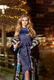 在典雅的配件礼服时兴的时髦的昂贵的皮大衣步行夜stre的美好的年轻性感的白肤金发的佩带的晚上构成 库存照片