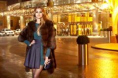 在典雅的配件礼服时兴的时髦的昂贵的皮大衣步行夜stre的美好的年轻性感的白肤金发的佩带的晚上构成 免版税库存图片