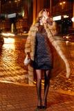 在典雅的配件礼服时兴的时髦的昂贵的皮大衣步行夜stre的美好的年轻性感的白肤金发的佩带的晚上构成 图库摄影