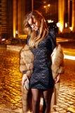 在典雅的配件礼服时兴的时髦的昂贵的皮大衣步行夜stre的美好的年轻性感的白肤金发的佩带的晚上构成 免版税库存照片