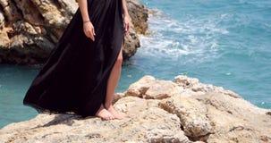 在典雅的黑礼服的美女腿在海附近 股票录像