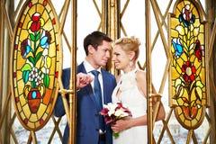 在内部污迹玻璃窗的新娘和新郎 免版税库存图片