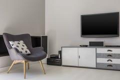 在内阁上的电视在有被仿造的pi的灰色扶手椅子旁边 库存图片