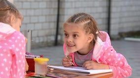 在册页的女孩图画与另一个女孩情感地讲话 影视素材