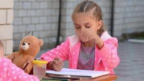 在册页绘的七年女孩在街道显示另一个孩子,参与与他的姐妹的绘画 影视素材