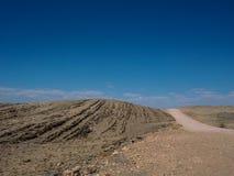 在冒险旅行的热的美好的天通过沙漠岩石山风景路线到与蓝天copyspace的空虚 图库摄影
