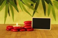 在写消息的宽度的小空的板岩在与红色石头专栏的竹地板上摆在了在与一个蜡烛的生活方式禅宗 免版税库存图片