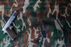 在军事伪装网背景的手枪 免版税库存照片