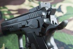 在军事伪装背景的火器手枪 免版税库存图片